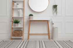 Console table with shelving unit and mirror on white wall in hallway. Interior design