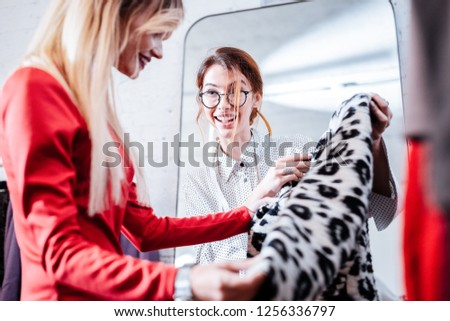 Constant client. Red-haired young shopping assistant consulting her constant client choosing new coat