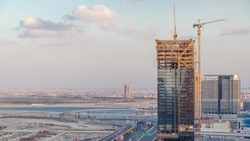 Construction activity in Dubai downtown with cranes and workers timelapse, UAE. Building of new skyscrapers and towers near crossroad junction