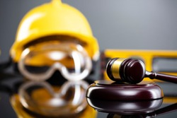 Construction and labor law concept. Judges gavel, yellow hard hat, level. Gray background.