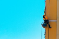 Construction and renovation background. Worker climbing on the wall