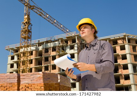Construction architects review plans at a construction site with crane