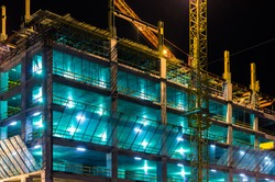 Construction at night with lights against the dark sky