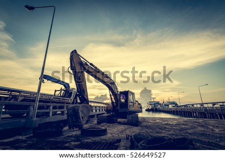 Construction at the pier with machinery during sunset