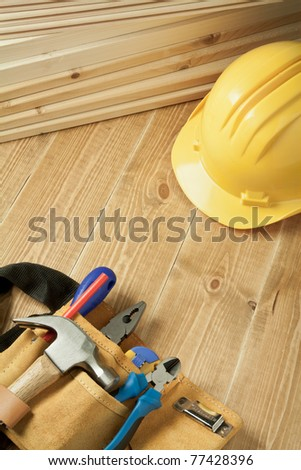 Construction background. Yellow helmet and tool belt on wooden floor.