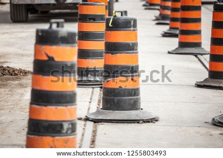 Construction barrels, north American style, on a renovation site on an asphalted street of downtown Toronto, Ontario, Canada. These plots are iconic of North American road system