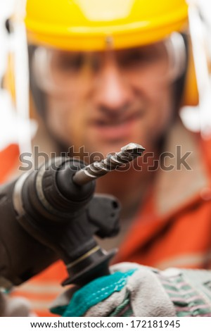 Construction building engineer or manual worker man in safety hardhat helmet hand holding electric hammer drill tool white isolated