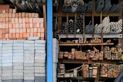 Construction building materials and industrial supplies such as bricks, woods and pipes stacked and arranged for sale at a hardware store front.