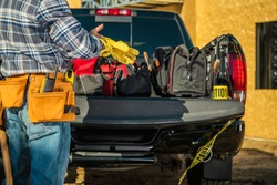 Construction Business Industry. Caucasian Contractor Worker Preparing Himself For the Job by Wearing Safety Gloves in Front of His Pickup Truck Full of Necessary Tools.