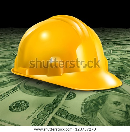 Construction business with a yellow hardhat helmet on a floor of money and currency representing the economic condition of commercial and residential building activity and investment.