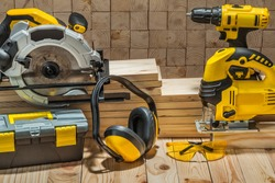 construction carpentry electric hand tools on wooden background