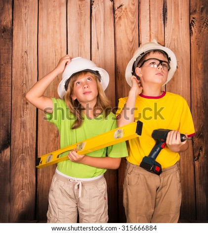 Construction children in hard hats and with tools thinking hard on wooden wall background. New house renovation concept.