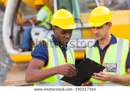 Construction Co-Workers Discussing About Work Plan Construction Site