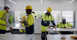 Construction company workers having takeaway lunch in modern office. Multiethnic team of engineers in safety uniform and hardhat taking food from table in office