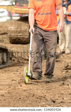Construction contractor laying out a dig line prior to digging a water line trench on a new commercial residential development
