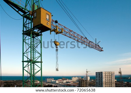 Construction crane against the blue sky and the houses under construction
