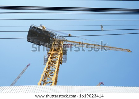 Construction crane and power lines with blue sky background. Low angle shot. stock photo