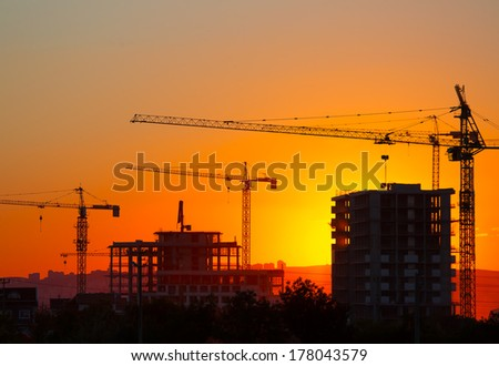 Construction crane and skyscraper at sunset  #178043579