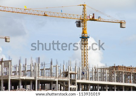 Construction crane at the construction site, on a cloudless sky