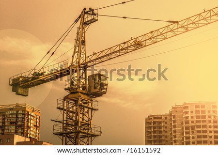 Construction crane. Construction crane against the background of two buildings in the evening.