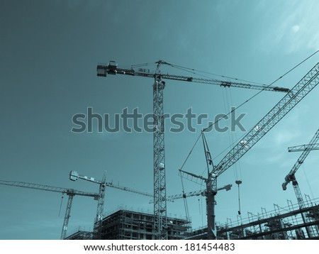 Construction crane for heavy weights lifting in building sites - cool cyanotype