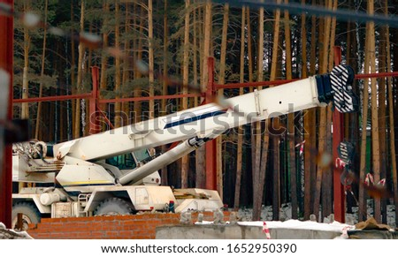 Construction crane in the middle of a construction site. Construction machine during the break.
