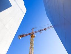 construction crane on blue sky background between buildings
