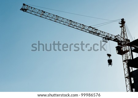 Construction crane  silhouette over sun