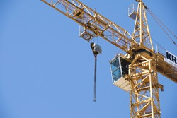 Construction crane tower on blue sky background. Crane and building working progress. Yellow lifting faucet. Empty Space for text. Construction concept. Site. New buildings with a crane. Tower crane