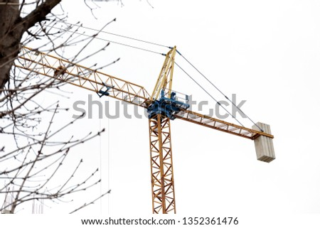 Construction crane tower on blue sky background. Crane and building working progress. Yellow lifting faucet. Empty Space for text. Construction concept. Site. New buildings with a crane. #1352361476