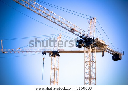 Construction cranes against blue sky