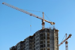 Construction cranes and unfinished residential building on background of clear blue sky. Housing construction, apartment block with scaffolding