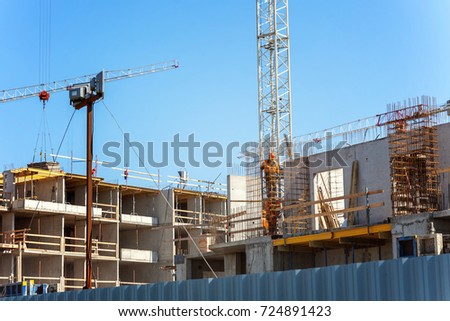 Construction cranes and workers on construction site against blue sky. building house, shop, mall or shopping center - Shutterstock ID 724891423