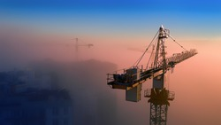 Construction cranes at dawn in the morning mist.