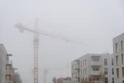 Construction cranes hidden in the fog on housing estate construction site