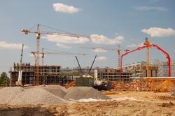 Construction cranes on a blue sky background