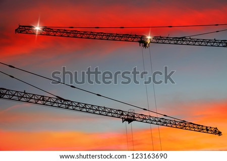 Construction cranes on sunset bright background