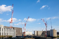 Construction cranes under bright blue sky and sun in Tokyo, Japan