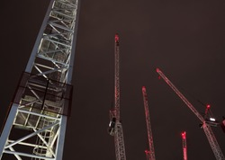 Construction cranes with red lights against a dark sky