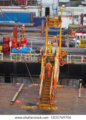 Construction crew crossing gangway from material barge to derrick lay barge.