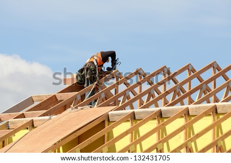 Construction crew working on the roof sheeting and outriggers or ladder of a new, two story, commercial apartment building in Oregon