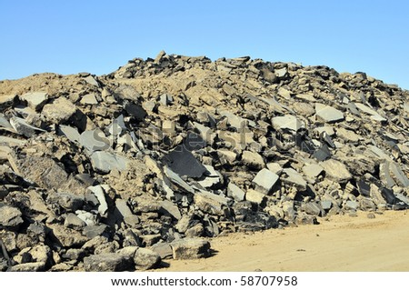 Construction demolition: Asphalt pile from road surface being replaced with new - stock photo