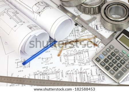 Construction drawings caliper bearing calculator pen ruler and glasses Desk Engineer
