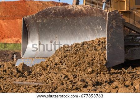 Construction Earthworks Dozer Excavator  Construction industrial earthworks dozer excavator  machine bucket pushing sand stones closeup abstract.