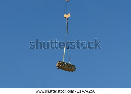 Construction elements being transported by jib crane over blue sky