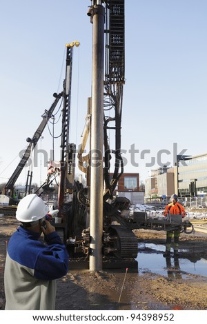 construction engineer directing giant excavator inside building-site, cranes and machinery