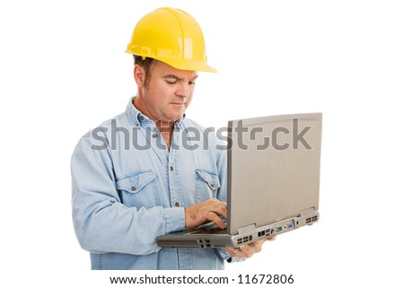 Construction engineer using his laptop computer on the job.  Isolated on white.