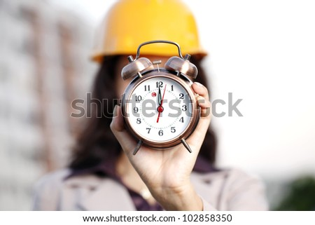 Construction engineer with alarm clock on face