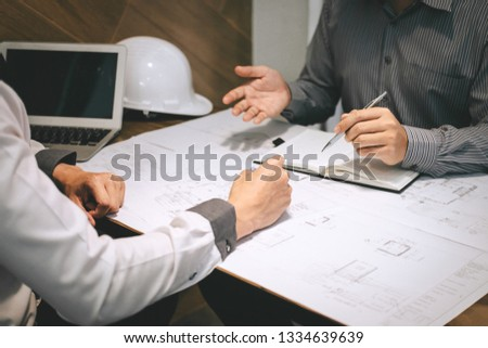 Construction engineering or architect discuss a blueprint while checking information on drawing and sketching, meeting for architectural project of partner. #1334639639