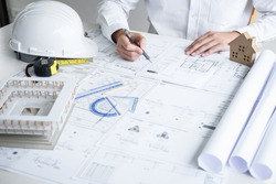 Construction engineering or architect hands working on blueprint inspection in workplace, while checking information drawing and sketching for architecture project working.
